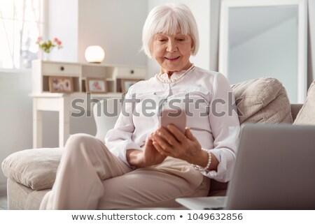 Stock photo: senior woman relaxing on the couch with her laptop