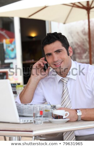 Businessman drinking an expresso in a cafe while talking on a cellphone Stock photo © photography33