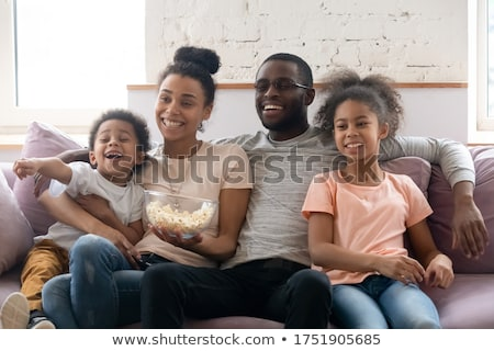 Stock fotó: Joyful Couple Watching A Movie With Pop Corn Sitting On The Sofa In The Living Room During The Day