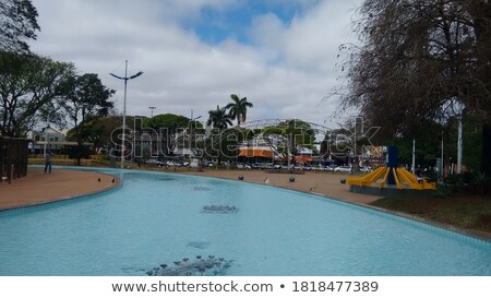 Image of palm trees around a water fountain. Stock photo © epstock