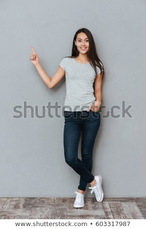 smiling happy girl posing in studio and pointing up stock photo © deandrobot