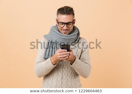 Szczęśliwy młody człowiek odizolowany beżowy mówić znajomych Zdjęcia stock © deandrobot