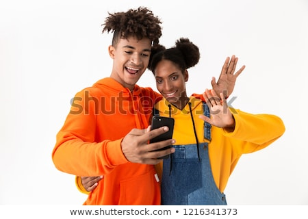 Photo of joyous couple man and woman taking selfie on mobile pho Stock photo © deandrobot