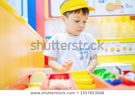 The boy plays in the seller of burgers Stock photo © galitskaya
