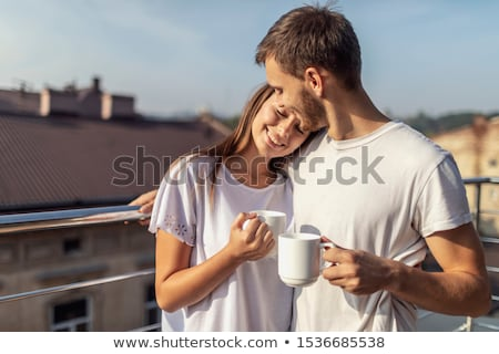 A young woman is having breakfast on the balcony. Breakfast table with coffee fruit and bread croisa Foto stock © galitskaya