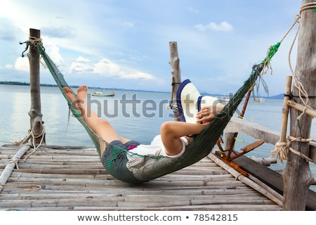 Woman wearing a straw hat lounging on a hammock by the beach Stock photo © photography33