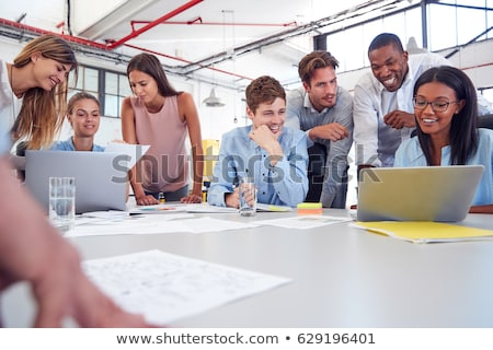 Co-workers gathered around computer screen Stock photo © photography33