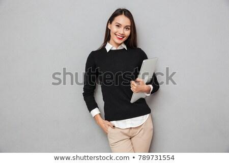 Businesswoman holding a laptop while smiling Stock photo © wavebreak_media