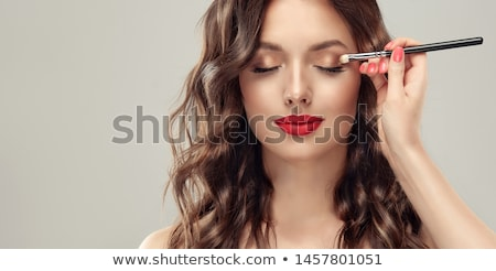 girl of a lip paints the professional visagiste with red  lipstick. Stock photo © fanfo