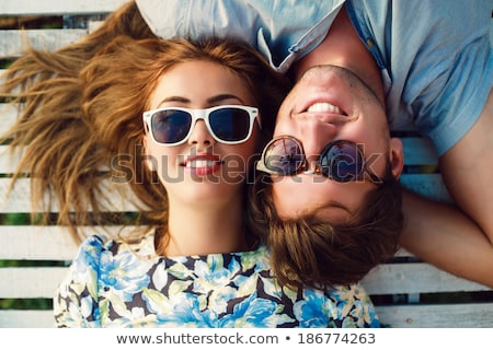 close up of young women lying on beach stock photo © dolgachov