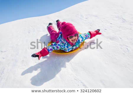 little girl riding on snow slides in winter time Stock photo © Lopolo