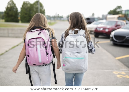 Portrait of two pre teenage girls studying outdoors in school yard Stock photo © Lopolo