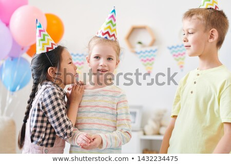 Cute little girl whispering something to one of her friends Stock photo © pressmaster