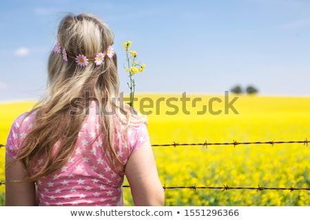 Kadın dikenli tel çit bakıyor alan çiçekli Stok fotoğraf © lovleah