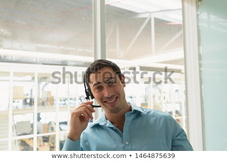 Portrait of handsome mixed-race male executive talking on headset in modern office Stock photo © wavebreak_media
