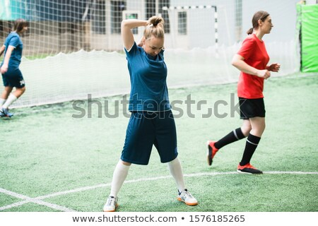 Blonde girl in blue sports uniform exercising on football field before game Stock photo © pressmaster