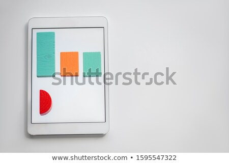 Colorful chart made up of flat wooden bricks lying in row on screen of tablet Stock photo © pressmaster
