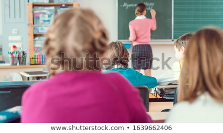 Teacher in class with fourth grade students in front of black board Stock photo © Kzenon