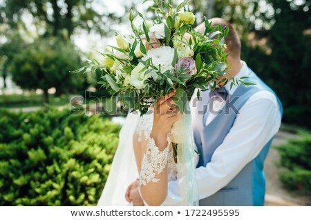 Cheerful newlyweds are hugging at their wedding and covering their face with a wedding bouquet Stock photo © ruslanshramko