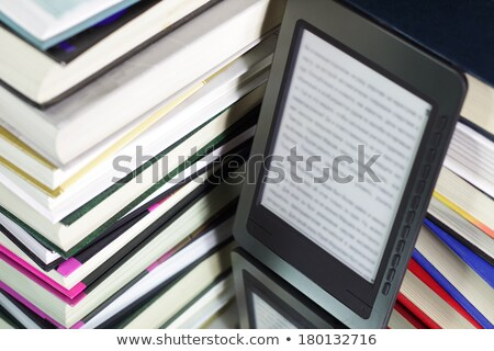 Foto stock: Stack Of Printed Books With Electronic Book Reader On Black Background