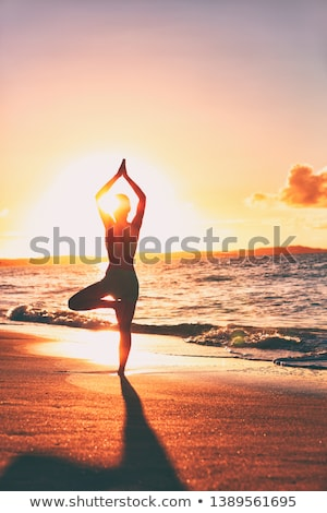 Yoga wellness retreat class on morning sunrise beach landscape. Silhouette of girl standing in tree  Stock photo © Maridav