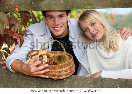 young couple behind trees in autumn, man holding a wickerwork basket Stock photo © photography33