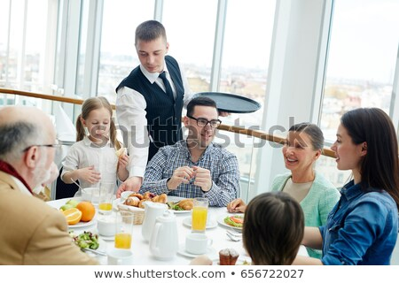 mature couple and young waiter at restaurant Stock photo © photography33