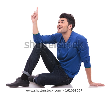 seated young casual man pointing at something up stock photo © feedough
