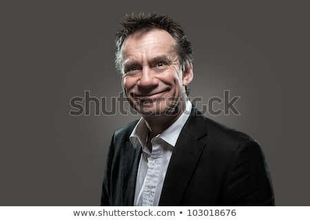 Business Man in Suit Pulling Face on Grey Grunge Look stock photo © scheriton