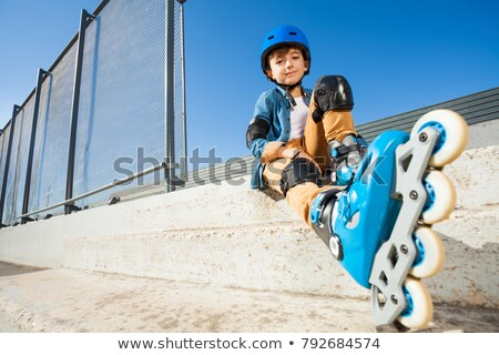 The boy with roller blades resting at the steps Stock photo © Traven