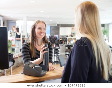 woman paying hairdresser in beauty salon shop Stock photo © diego_cervo