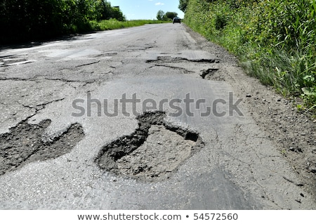 Broken pavement and pothole asphalt road after winter. Stock photo © 5xinc