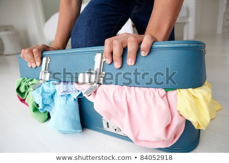 Teenage boy struggling to close suitcase Stock photo © monkey_business