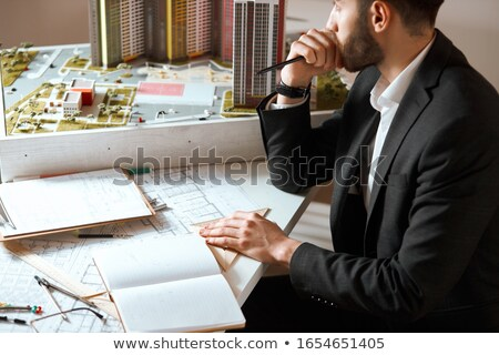 Thoughtful creative man designing project and making blueprint Stock photo © deandrobot