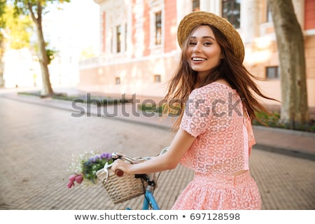 Fashionable girl riding bike and looking at camera stock photo © cienpies