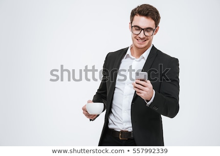 man in eyeglasses holding cup of coffee and looking away stock photo © deandrobot
