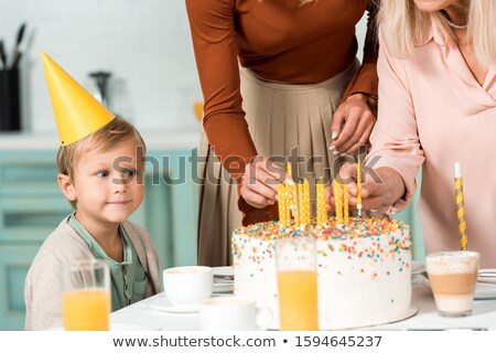 Woman at party putting candles in cake on food table smiling Stock photo © monkey_business