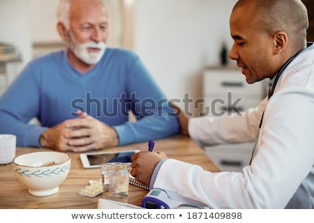 Сток-фото: General Practitioner Writing Notes During Medical Exam