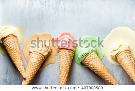 Green and yellow melting ice cream with waffle cone and scoop on Stock photo © artjazz