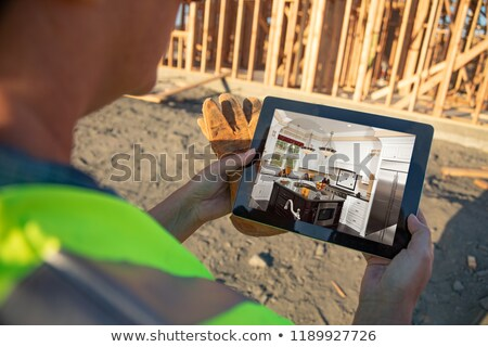 Female Construction Worker Reviewing Kitchen on Computer Pad at  Stock photo © feverpitch