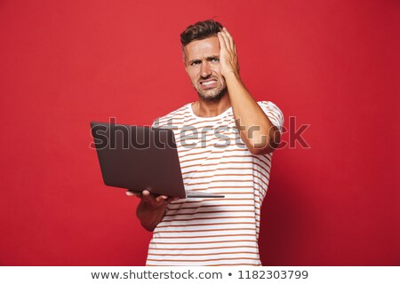 Kép zavart fiatalember csíkos póló mosolyog Stock fotó © deandrobot