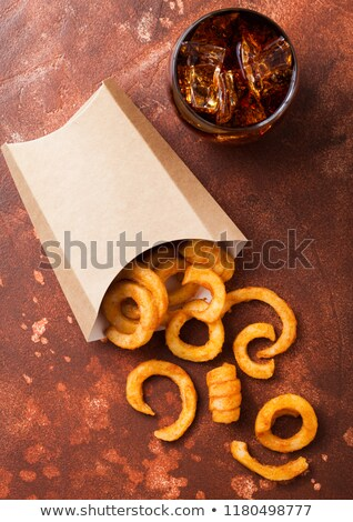Curly fries fast food snack in paper container with glass of cola on rusty stone kitchen background. Stock photo © DenisMArt