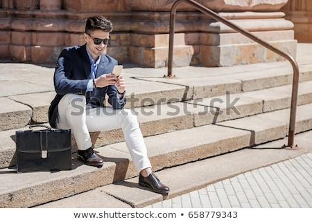 handsome young man wearing leather jacket and sunglasses sitting stock photo © feedough