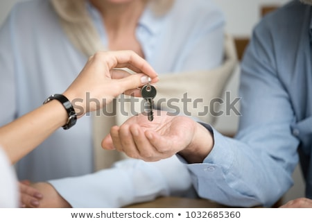 realtor woman giving house keys to couple closeup stock photo © kzenon
