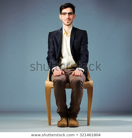 smiling businessman in black suit sitting on wooden chair Stock photo © feedough