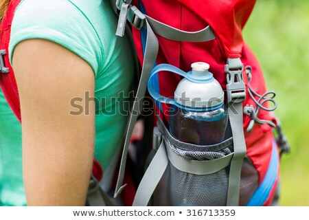 close up of woman with water bottle in backpack stock photo © dolgachov