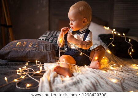 baby boy plays with garland of glowing light bulbs stock photo © stasia04