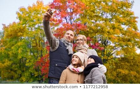 family taking selfie over autumn park background stock photo © dolgachov