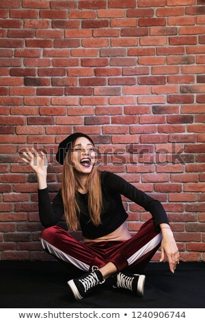 Photo of happy hip hop dancer or sporty woman, sitting on floor  Stock photo © deandrobot