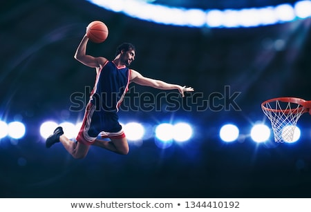 Acrobatic slam dunk of a basket player in the basket at the stadium Stock photo © alphaspirit